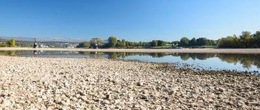 与石头的干燥河床,可看见的老铁路桥 免版税图库摄影