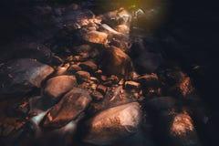 与石头美好的太阳光银行的瀑布  库存图片