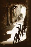 与石房子和自行车的古老被修补的通道 免版税库存照片