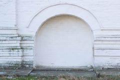 与石曲拱的被围住的门在古老白色涂了灰泥墙壁背景,照片框架 库存图片