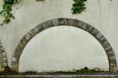 与石曲拱e以老米黄涂灰泥的墙壁为背景,相框,文本地方的一个被围住的门 免版税库存照片