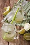与石灰、冰和迷迭香的冷的柠檬水接近在玻璃ja 库存图片