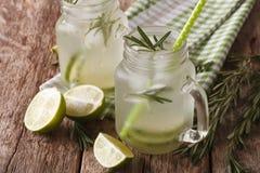 与石灰、冰和迷迭香的夏天冷的饮料接近在glas 库存图片