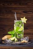 与石灰、姜、薄菏和阳桃的明亮的mojito鸡尾酒在木背景的一块透明玻璃 复制空间 免版税库存图片