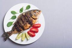 与石灰、蕃茄和菠菜的油煎的鱼dorado 鱼食物荷兰芹牌照烤海运 库存图片