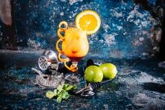 与石灰和伏特加酒的橙色鸡尾酒 与石灰、柠檬和冰的饮料酒精饮料在餐馆为寒冷服务 库存图片