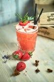 与石灰和冰的草莓柠檬水在一个木桌JPG的金属螺盖玻璃瓶 库存照片