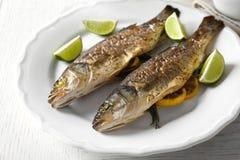 与石灰和柠檬的两条被烘烤的鱼 库存图片