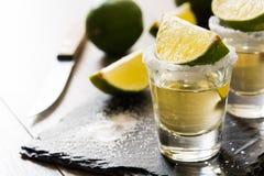 与石灰和盐的墨西哥金子龙舌兰酒在木头 库存照片