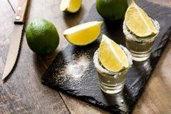 与石灰和盐的墨西哥金子龙舌兰酒在木头 库存图片