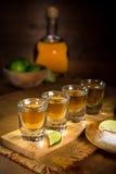 与石灰和盐的金黄龙舌兰酒射击服务在墨西哥餐馆桌上 免版税库存图片