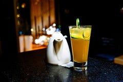 与石灰和茶壶的橙色鸡尾酒在黑暗的背景 免版税库存图片