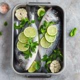 与石灰和荷兰芹的两条未加工的dorado鱼准备好对烹调 库存图片