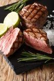 与石灰和迷迭香关闭的新近地煮熟的可爱的里脊肉牛排 库存图片