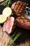 与石灰和迷迭香接近的烤小腓厉牛排 垂直 免版税图库摄影
