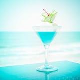 与石灰果子和樱桃装饰的蓝色玛格丽塔酒鸡尾酒 库存照片