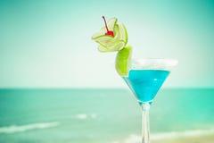 与石灰果子和樱桃装饰的蓝色玛格丽塔酒鸡尾酒 库存图片