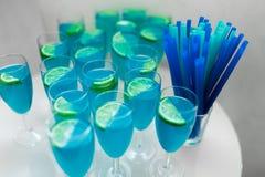 与石灰的一些蓝色鸡尾酒在桌上 免版税库存图片
