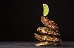 与石灰的可口热带海软体动物 四只美丽的闭合的牡蛎特写镜头在黑背景的 复制空间 库存照片