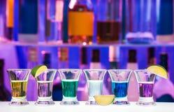 与石灰的小玻璃在行,酒吧瓶支持 免版税图库摄影