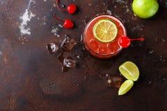 与石灰的红色鸡尾酒在棕色桌背景 库存图片