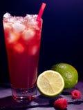 与石灰的红草莓鸡尾酒在黑暗 库存图片