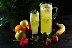 与石灰的绿色苹果柠檬水在水罐和玻璃和果子在黑暗的背景 免版税库存图片