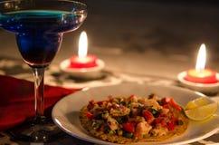 与石灰的虾炸玉米粉圆饼和蓝色鸡尾酒和蜡烛 库存照片