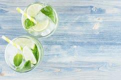 与石灰,叶子薄菏,秸杆,冰块,在蓝色木背景,顶视图,边界的苏打的新鲜的冷的夏天饮料mojito 免版税库存图片