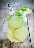 与石灰,在一个金属螺盖玻璃瓶的薄菏的自创柠檬水在一张木桌上 免版税库存照片