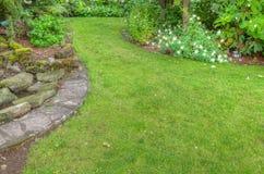与石边缘的环境美化的庭院场面 免版税库存照片