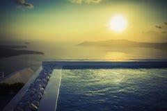 与石头的无限水池在日落在圣托里尼海岛 库存图片