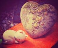 与石头般的心的陶瓷猫 免版税库存图片