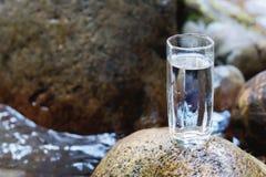 与矿物山河水的一块透明玻璃玻璃在山河小河旁边的一块石头站立 免版税库存照片