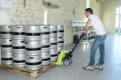 与码垛车的人移动的桶啤酒 免版税图库摄影