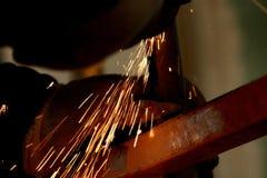与研磨机机器和火花的工作者研的切口金属板 库存图片