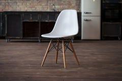 与砖墙和灰色木地板的概念性空的白色木脚椅子 图库摄影