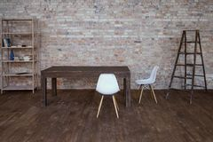 与砖墙和灰色木地板的概念性空的白色木脚椅子 免版税图库摄影
