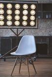与砖墙和灰色木地板的概念性空的白色木脚椅子 库存照片