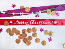与硬币、小珠、雪花、丝带和圣诞快乐刷子书法的平的位置构成  图库摄影