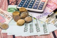与硬币和计算器的欧元票据 库存图片