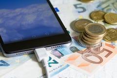与硬币概念的电话和金钱欧元 库存图片