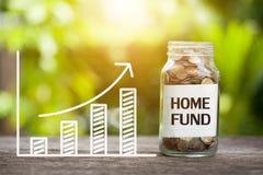 与硬币的家庭资金词在玻璃瓶子和图表 财政Co 免版税图库摄影
