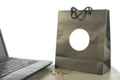 与硬币的纸购物袋和计算机,在桌上的膝上型计算机 免版税图库摄影
