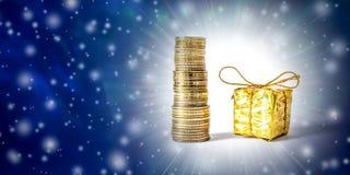 与硬币的美好的圣诞节和新年的背景和在金子包装的礼物盒 免版税图库摄影