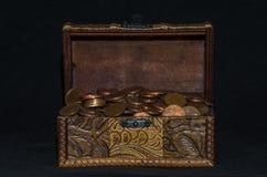 与硬币的老箱柜在黑背景 免版税库存照片