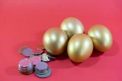 与硬币的金黄鸡蛋在概念投资或复活节 免版税库存照片