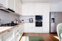 与硬木地板和木白色乳脂状的家具的现代厨房内部 免版税库存照片