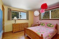 与硬木地板和桃红色墙壁的可爱的女孩卧室内部 库存照片
