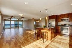 与硬木地板和米黄墙壁的宽敞厨房内部 图库摄影